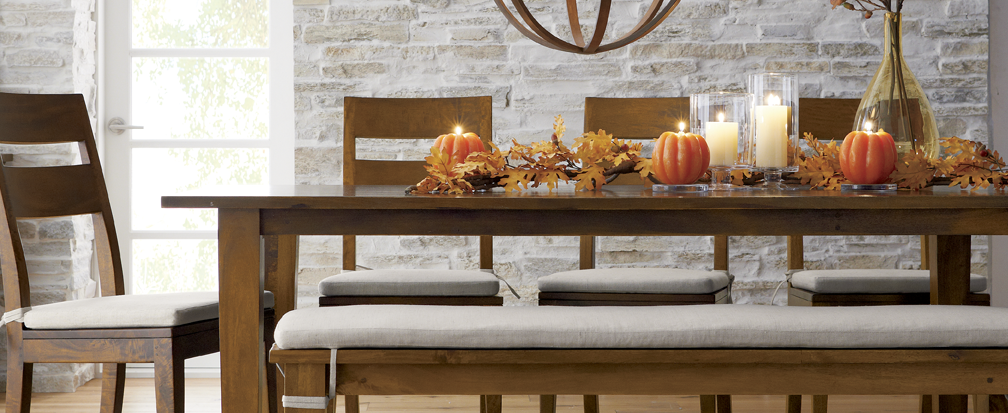 Pumpkin candles and decorative leaves on a brown wood dining room table