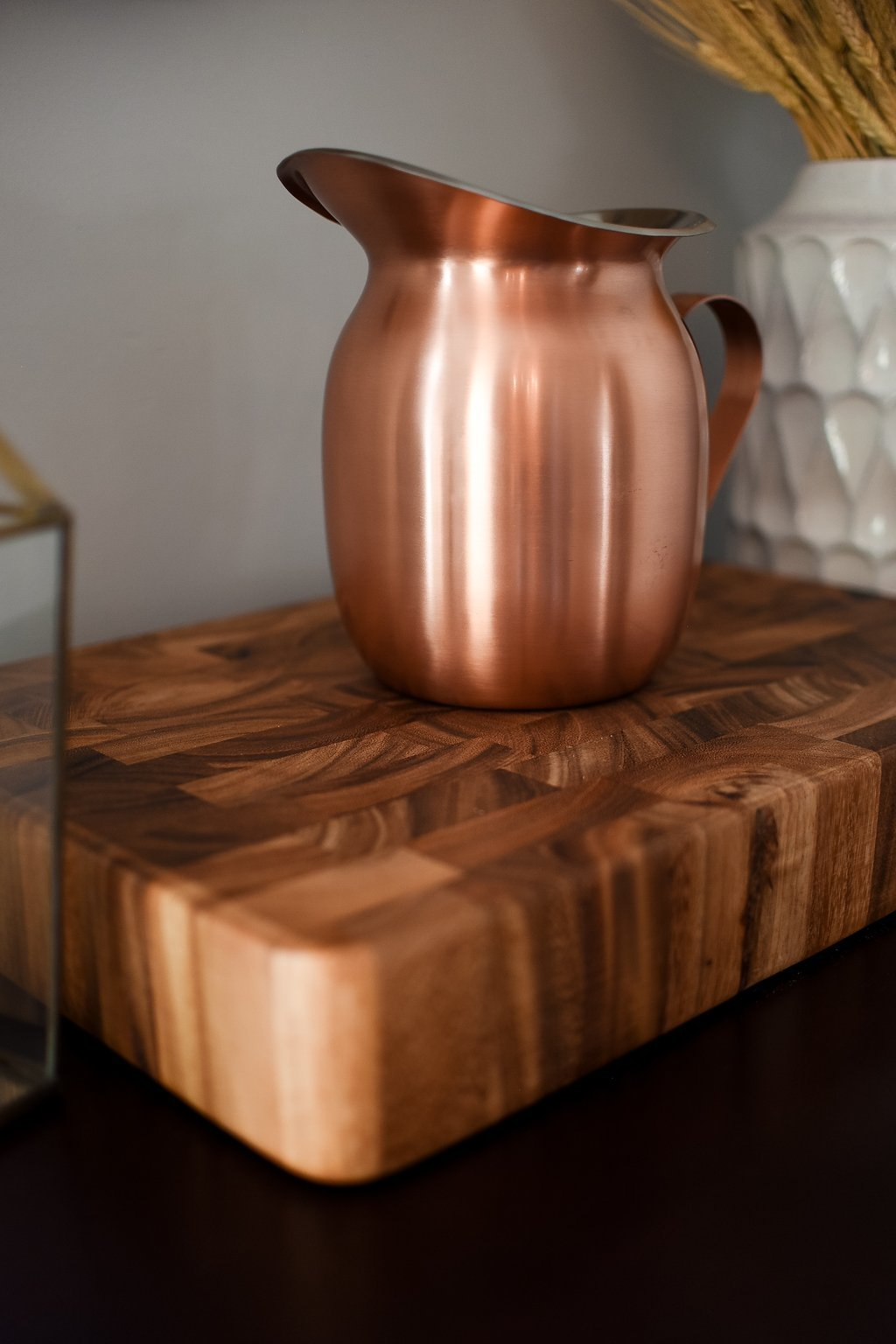 Copper pitcher on a wood serving platter