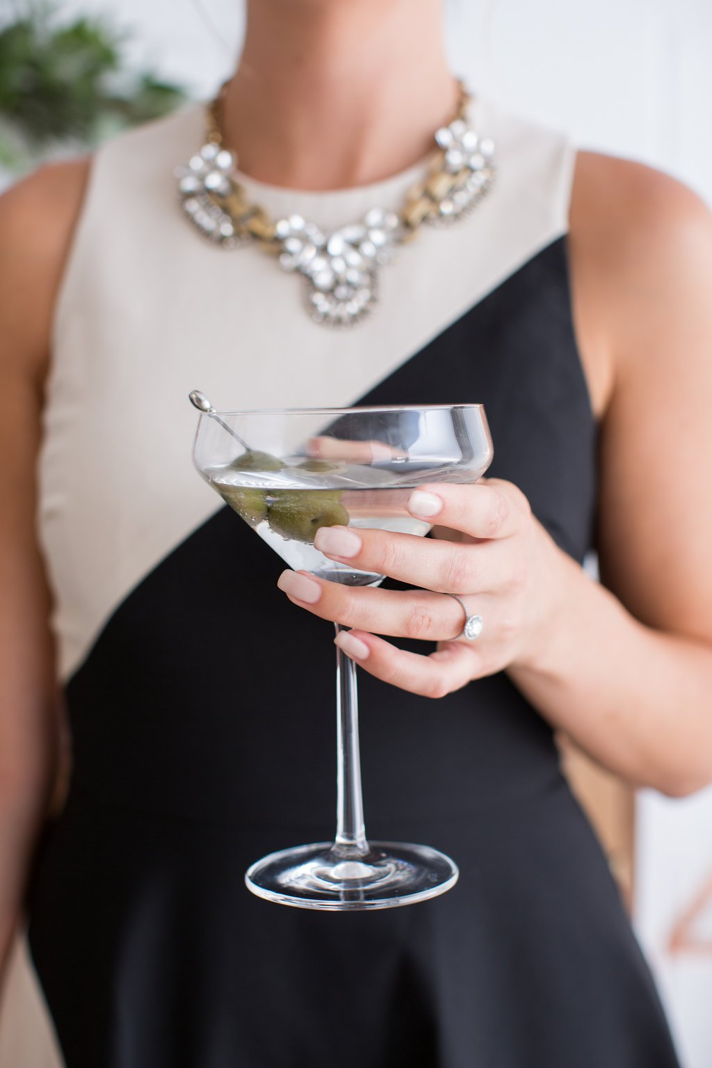 a woman holding a martini glass with two olives on a stick