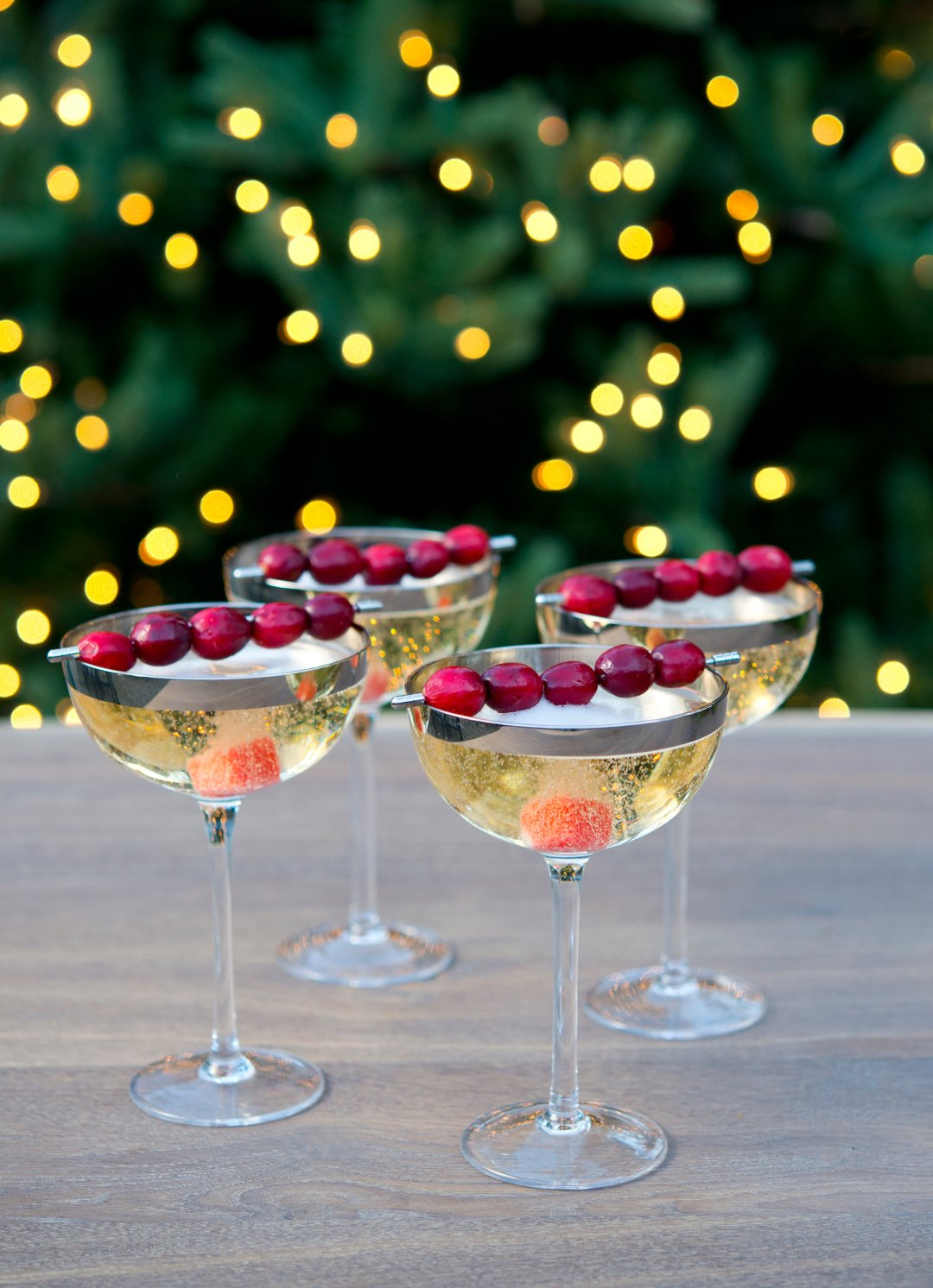 four glasses of champagne with cranberries on a table in front of a christmas tree