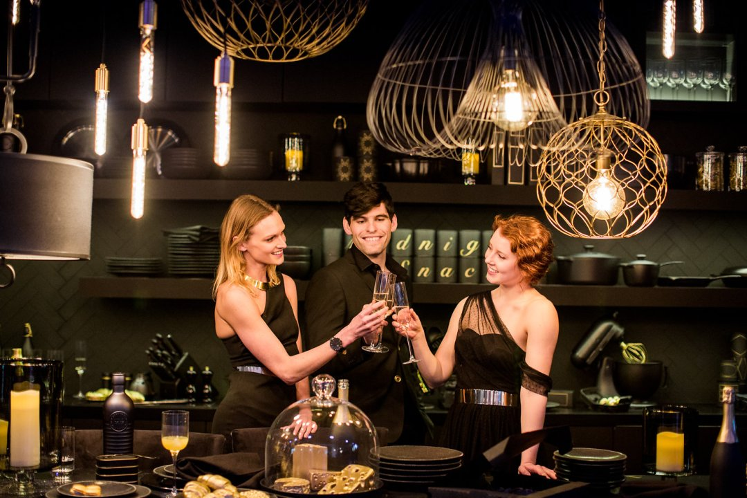 Two women and a man behind the table toasting with champagne