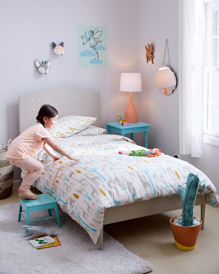 A young girl climbs on a stool into her twin bed.