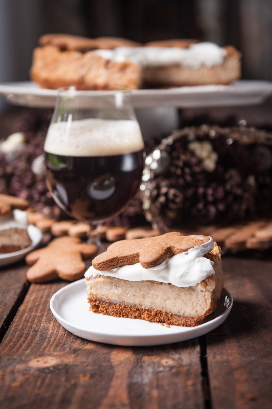 Single slice of gingerbread cheesecake topped with a gingerbread man cookie on a small white plate