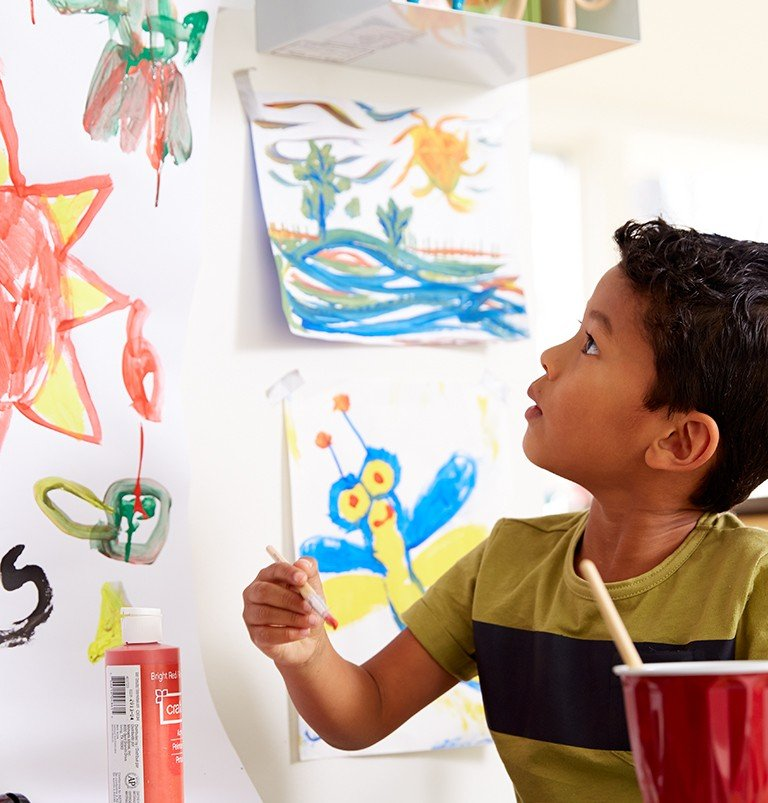 In the arts and crafts area of a playroom, a young boy paints pictures