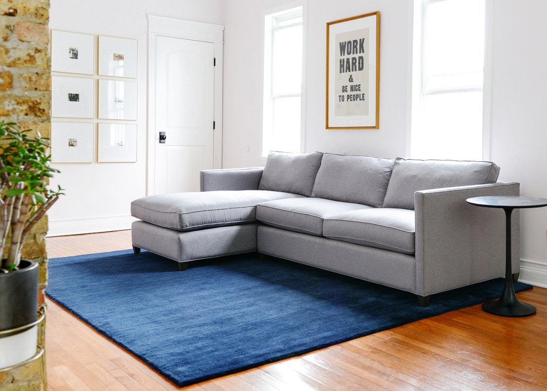 Studio living space with dryden sofa in a grey fabric on a midnight blue area rug