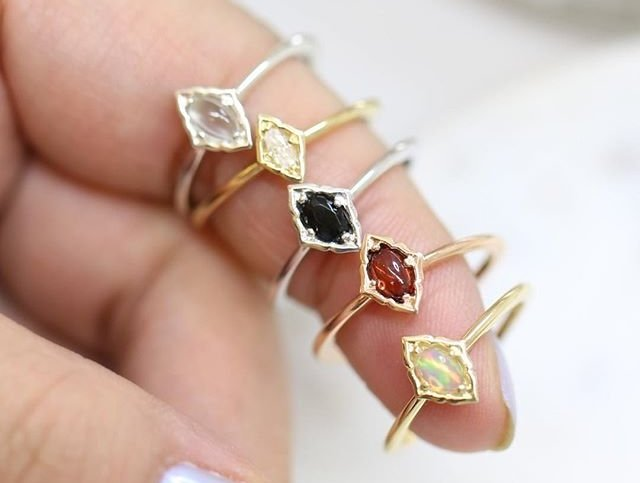 An index finger holding 5 engagement rings colored silver, gold and rose gold with gemstones.