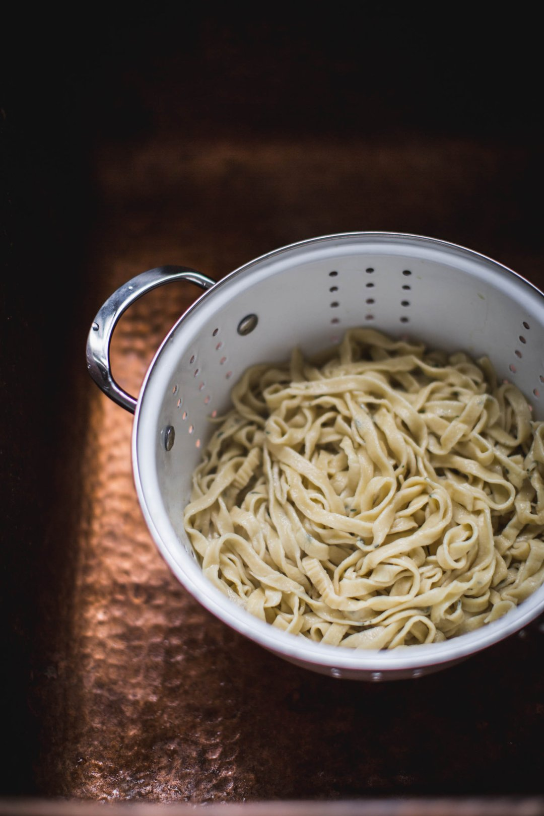 a large colander containing freshly cooked linguine