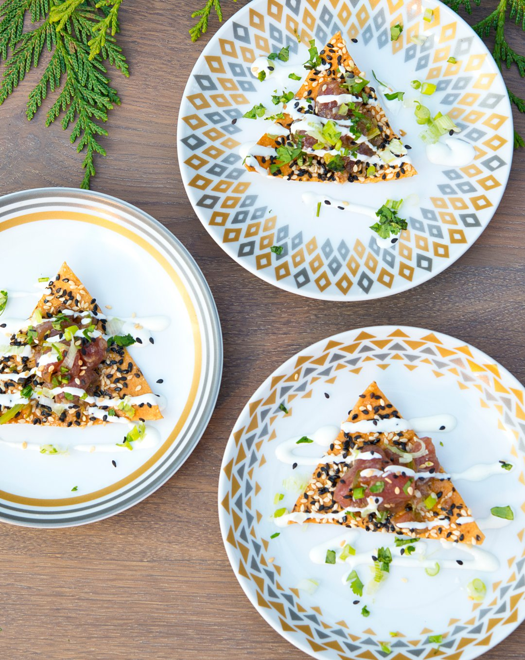 three plates with appetizers on a table with a tree branch