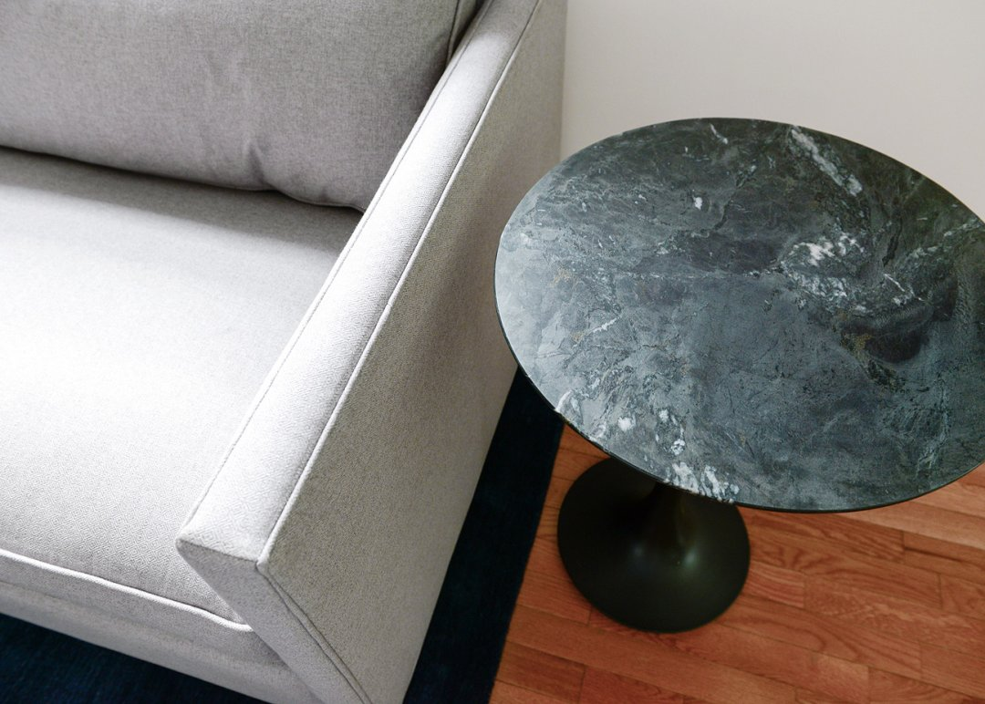 Black marble side table arranged next to a small grey sofa