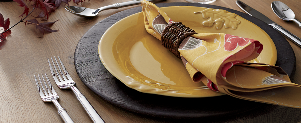 Dinner table with yellow-orange plate and autumnal napkin in wicker ring