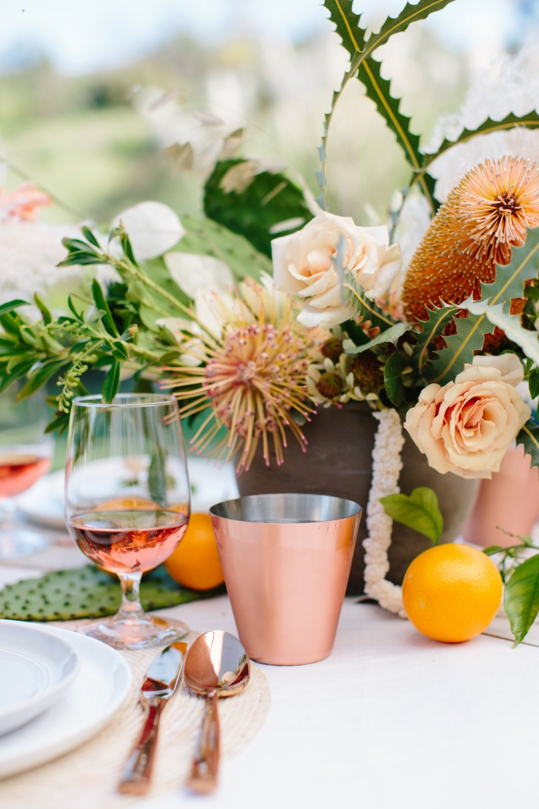 Copper glass and wine glass filled with rose wine next to place setting