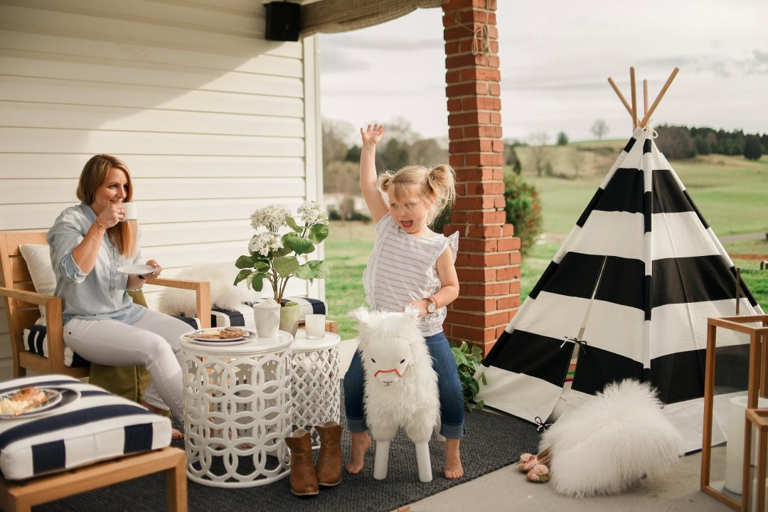 Little girl riding llama rocking horse while mother smiles watching from behind