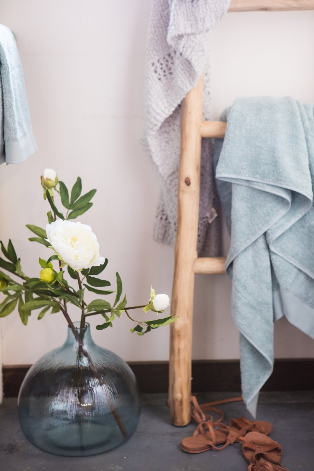 Ladder with towels and blue vase with flowers