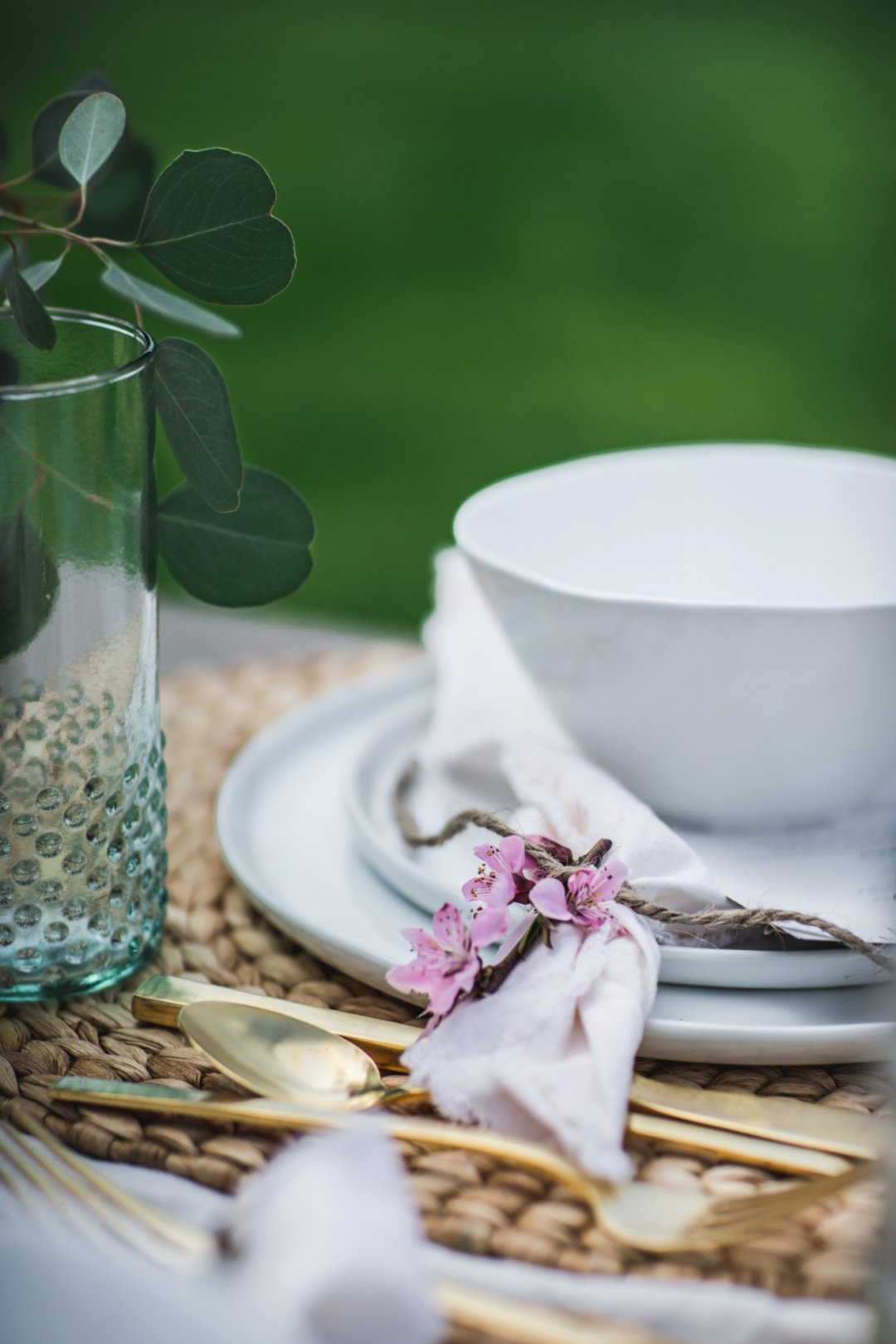 Close up of bowl and plates with silverware and glassware, along with a napkin tied with a flower