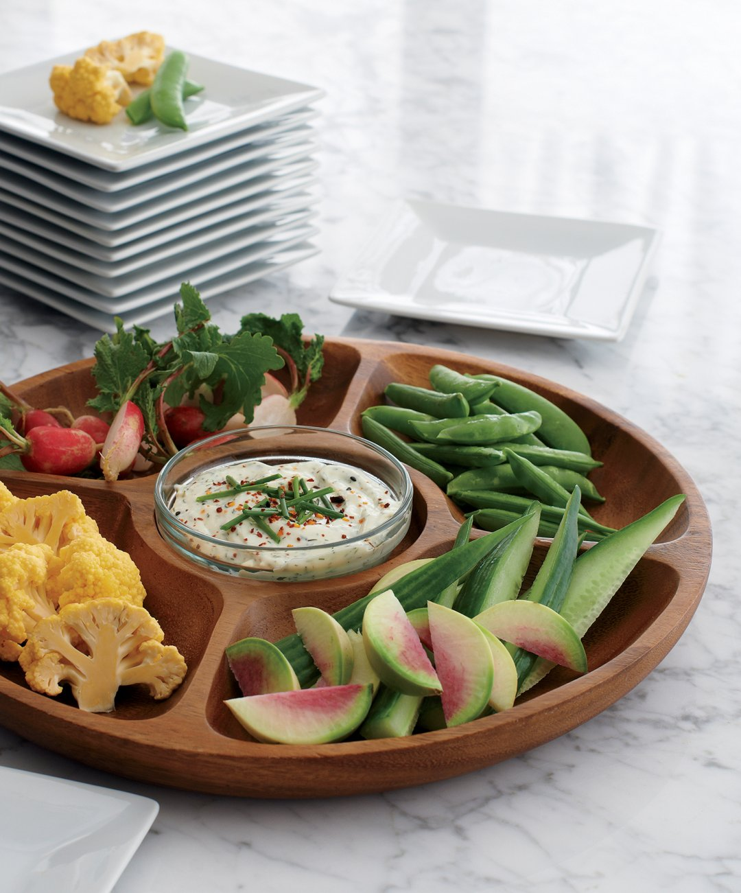 Selection of veggies served in a wooden dish with dip