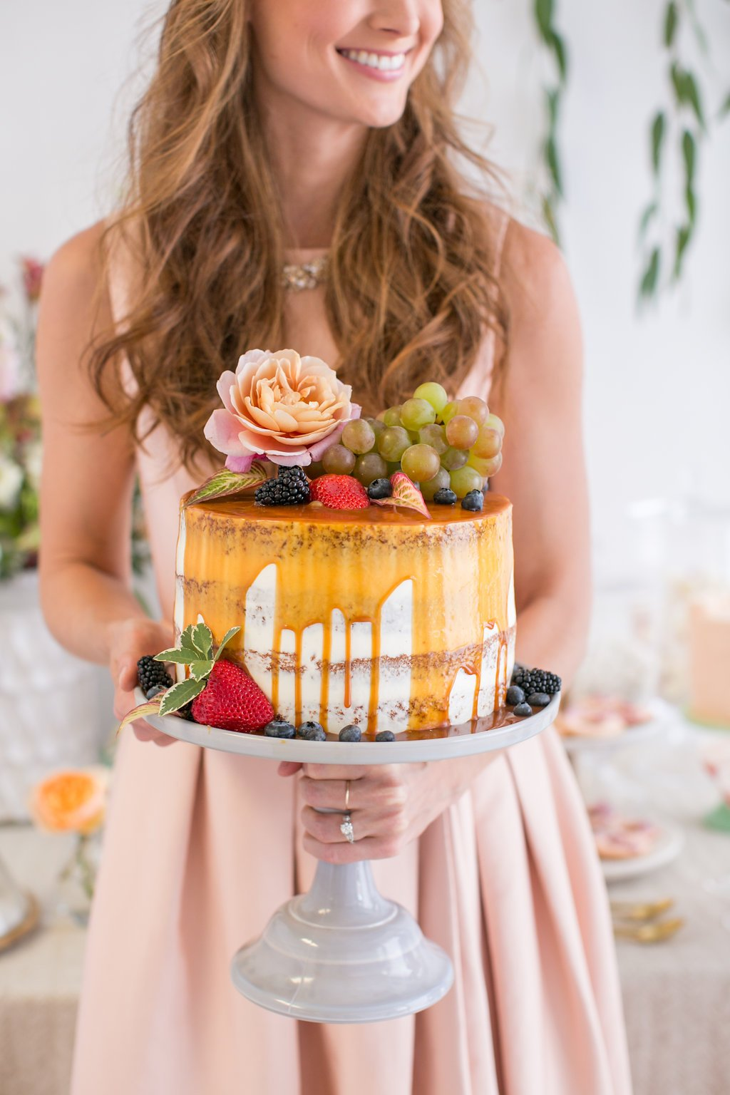 Bride holding caramel drizzled wedding cake at spring bridal shower