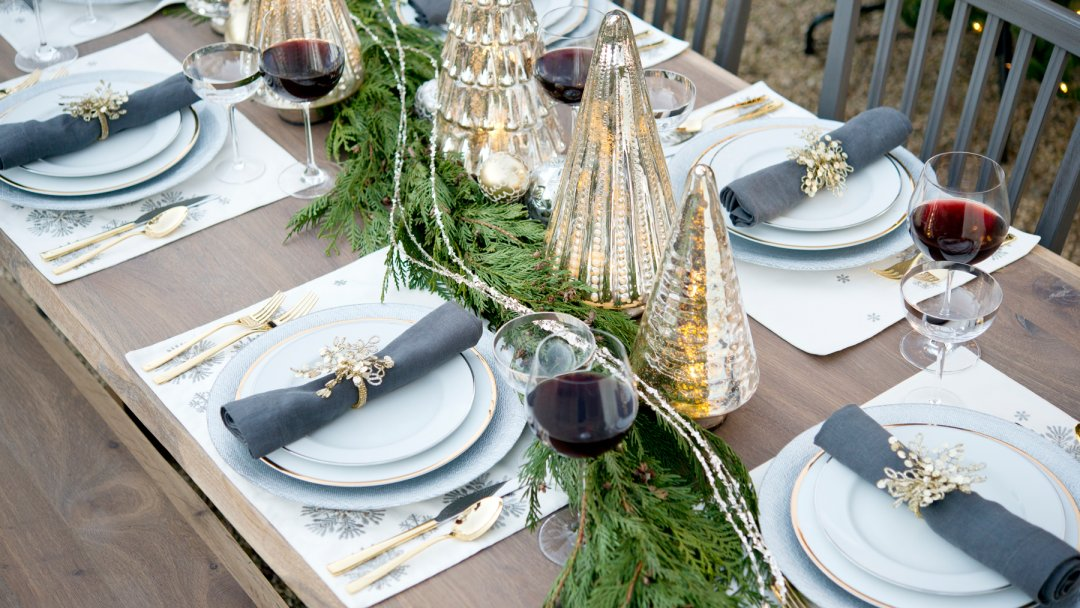 table full of plates wine glasses glass trees and tree branches