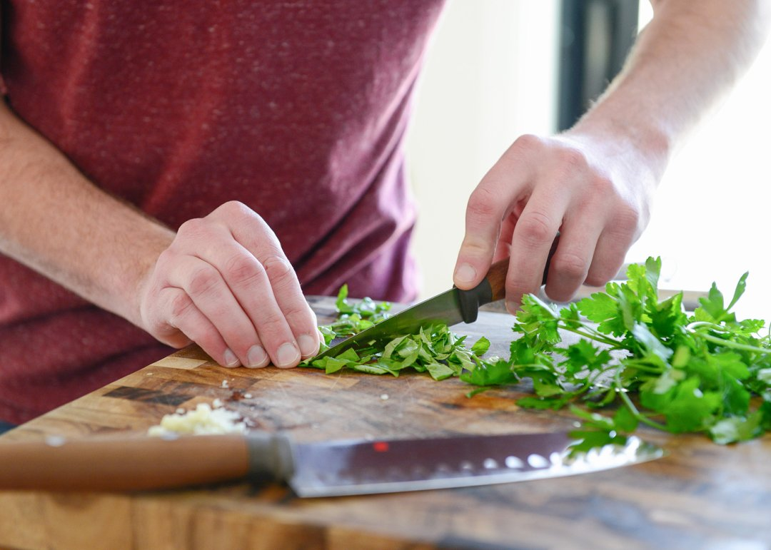 Chopping herbs on cutting board with a knife