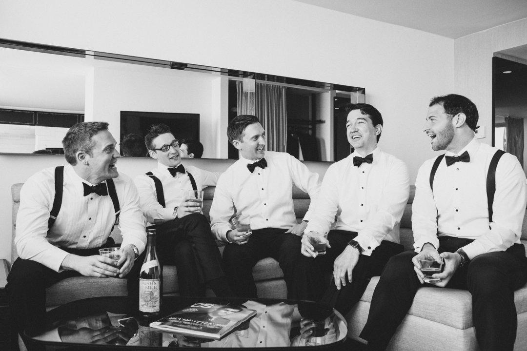 Groom and groomsman drinking and talking