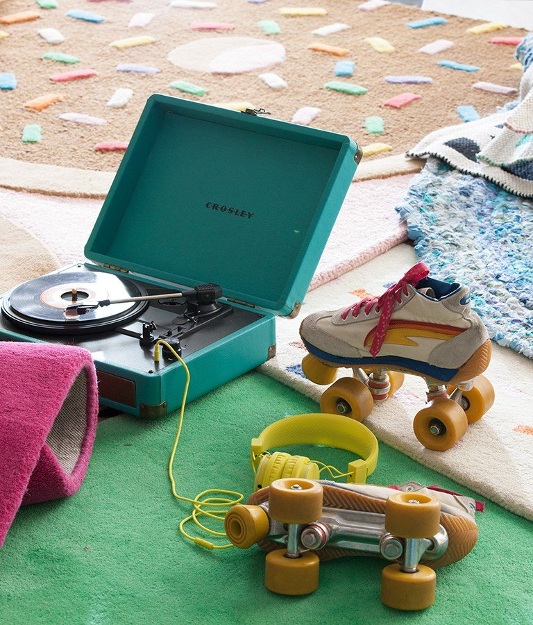 Retro roller skates and a record player rest on a series of wool rugs.