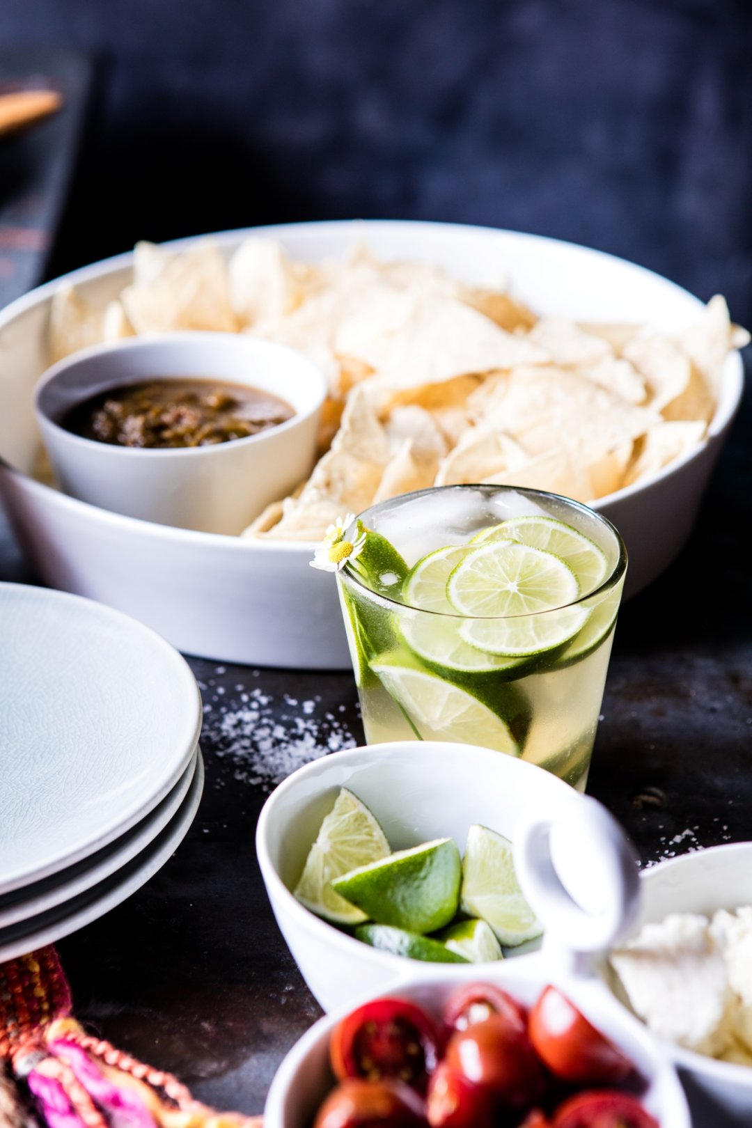 Glass with margarita and limes in front of chips and salsa with stack of plates to the left and 3-part server with condiments in front