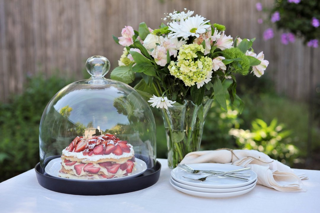 Flower vase with flowers, dessert in cloche, and plates