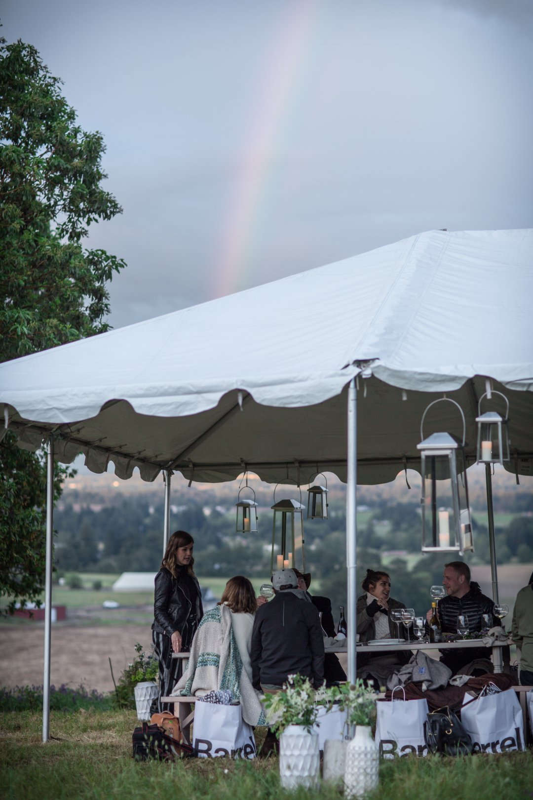 Tent with people underneath and rainbow in background