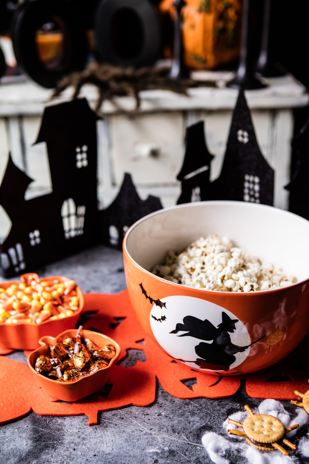 Popcorn, candy corn and chocolates in orange halloween bowls on the snack table