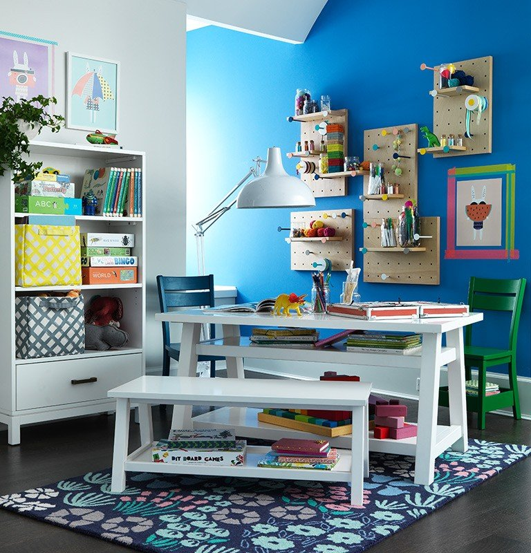 A play table in a playroom with wall shelves and bookshelves.