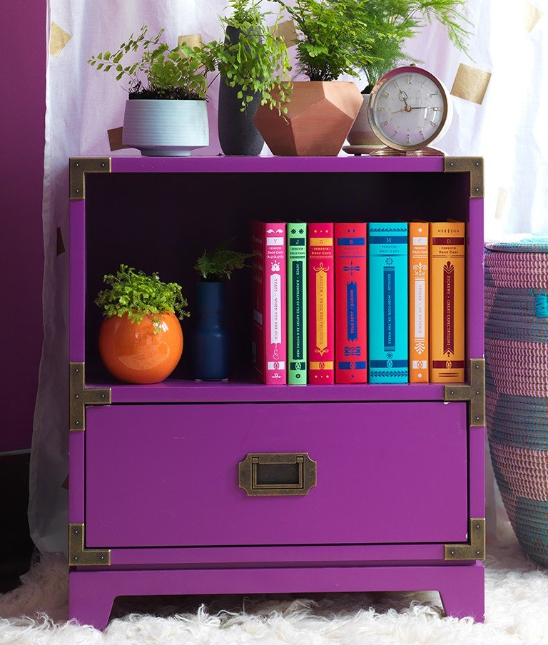 A bold purple campaign night stand and hamper