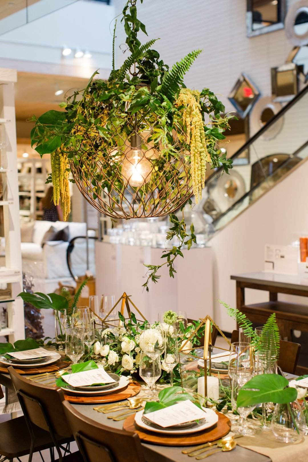 Chandelier with greenery over set table