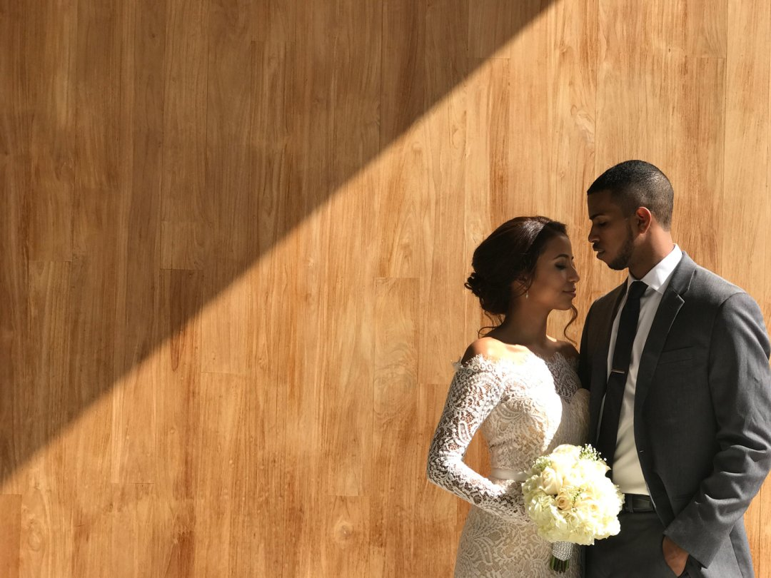 Bride and groom standing against wood background