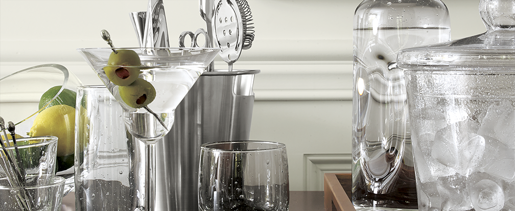 Stocked home bar with martini glasses, cocktail shaker, ice bucket and other barware