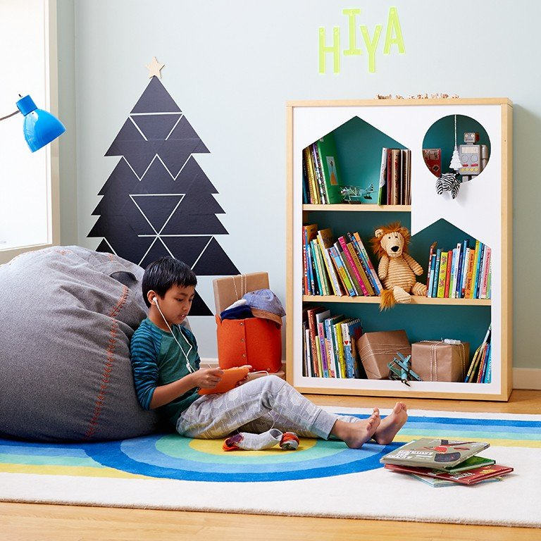 A young boy leans against a bean bag chair while playing