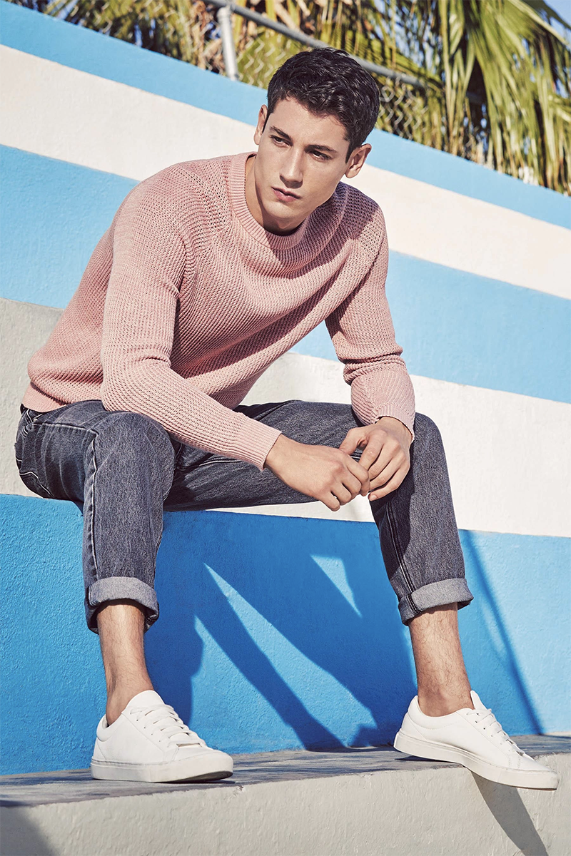 Men's pink sweater and washed black jeans