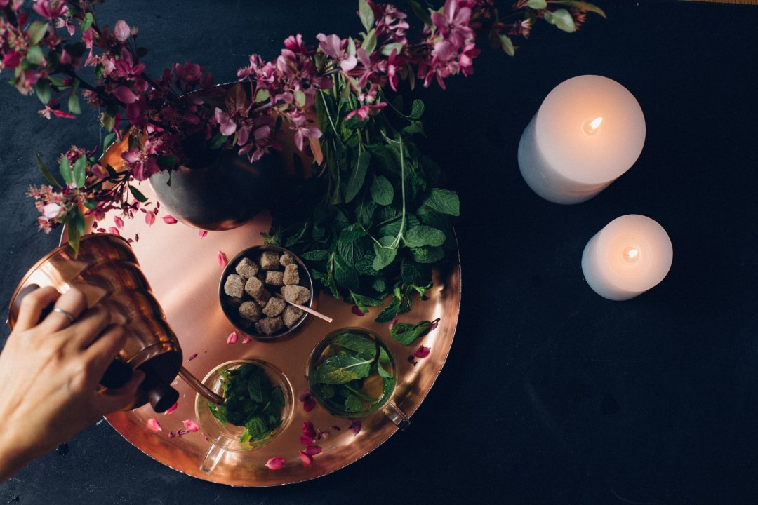 Lit candles next to copper tray with hands pouring hot water into tea cups from copper kettle with flower pot and sugar next to it