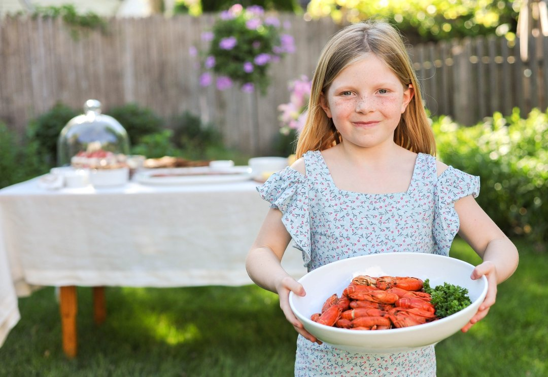 Little girl holding platter with seafood