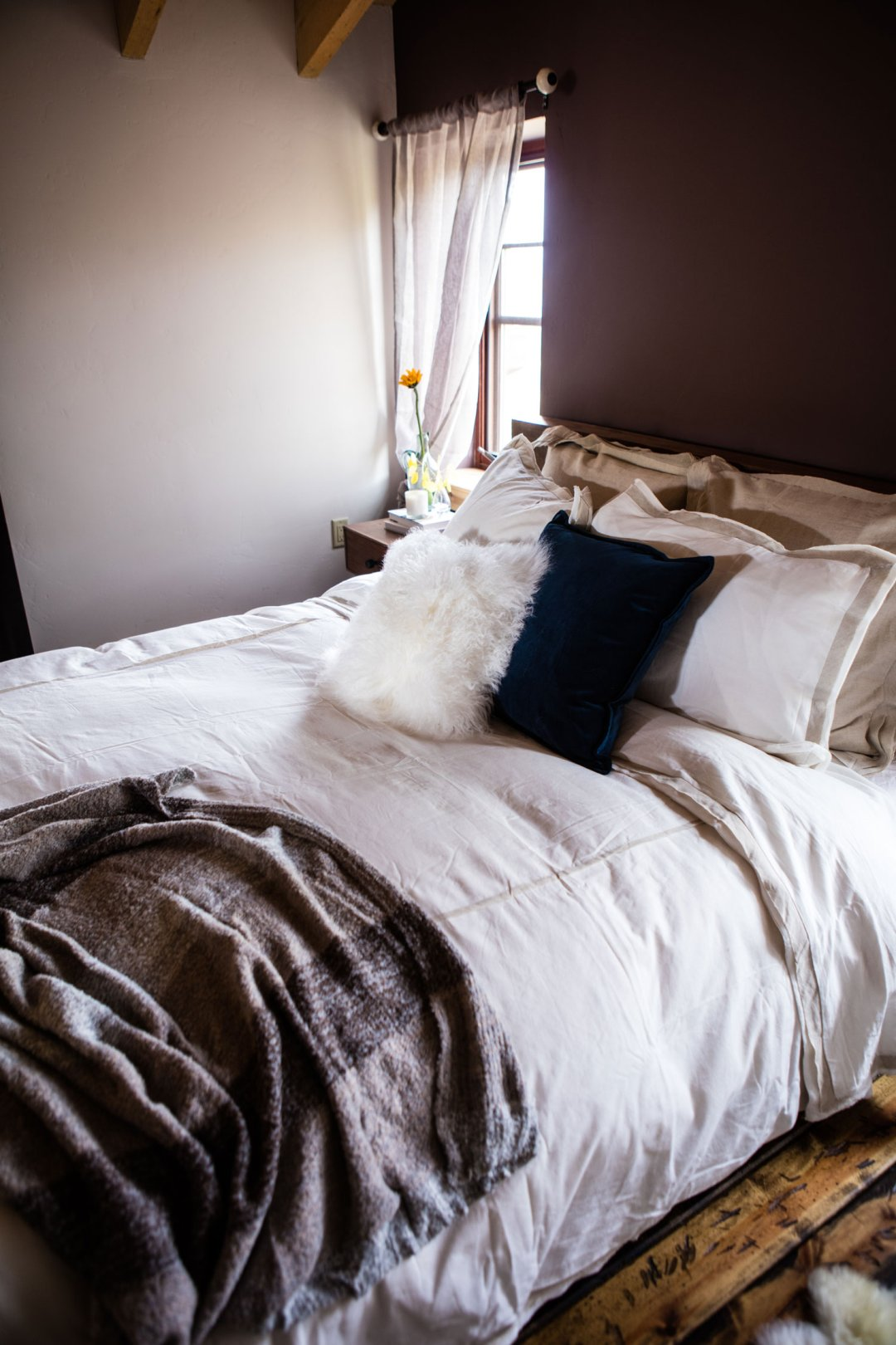 White bedding and duvet with a decorative white fur pillow and blue velvet pillow