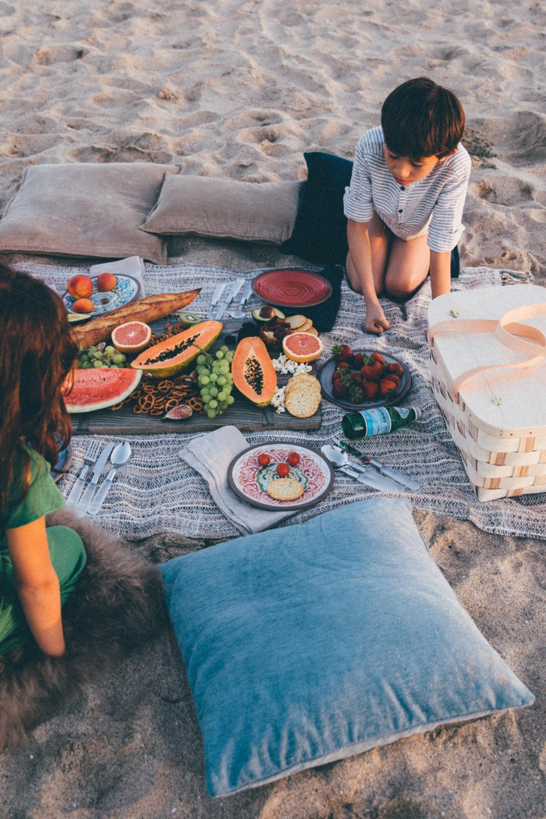 Pillows around blanket with picnic foods and kids eating