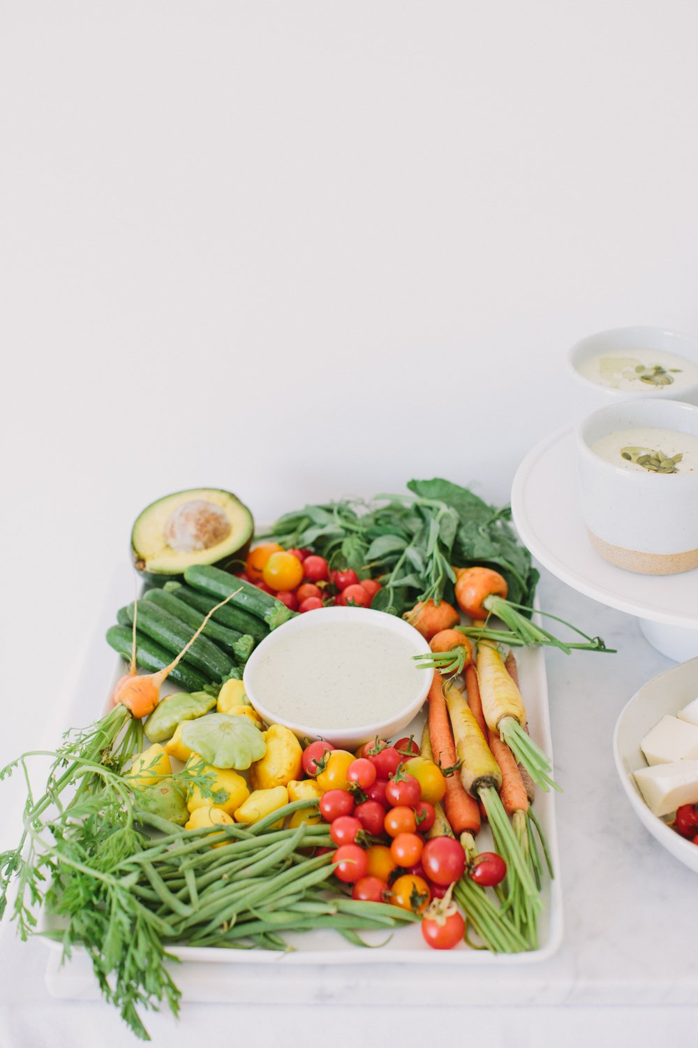 Fresh herbs, avocado, carrots, zucchini and cherry tomatoes arranged around a creamy dip on a large white serving tray