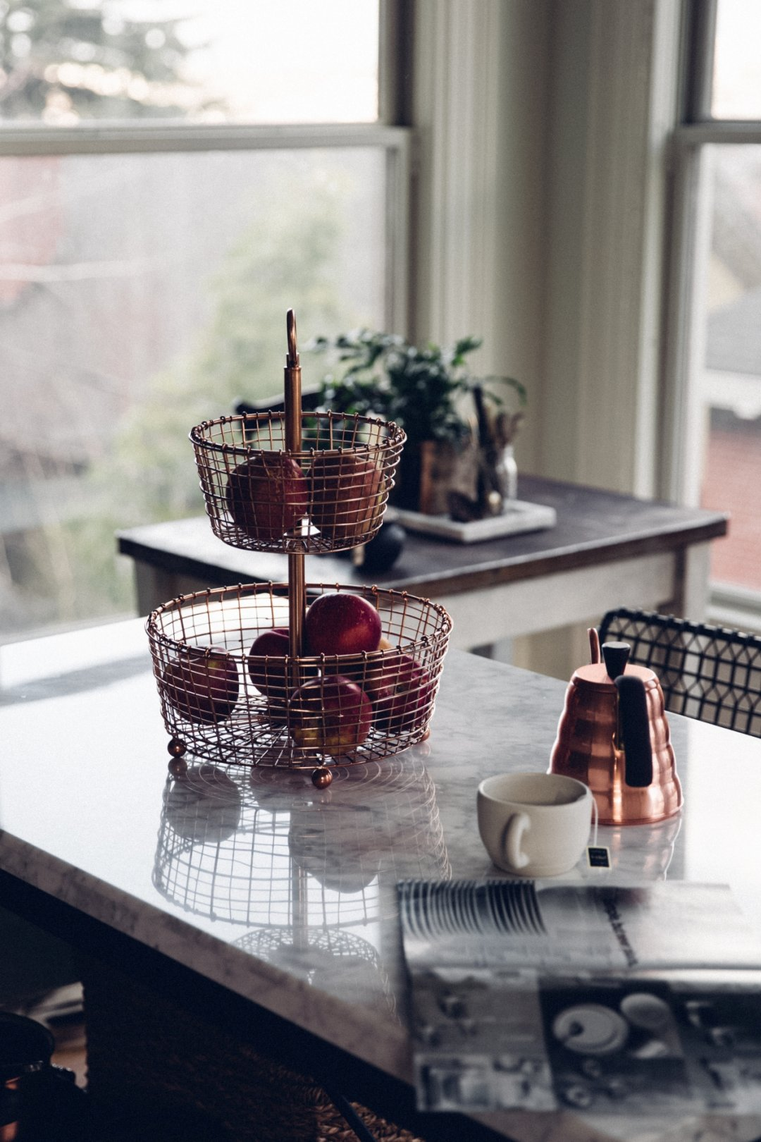 Kitchen island with 2-tier copper fruit basket and copper kettle, with mug steeping tea