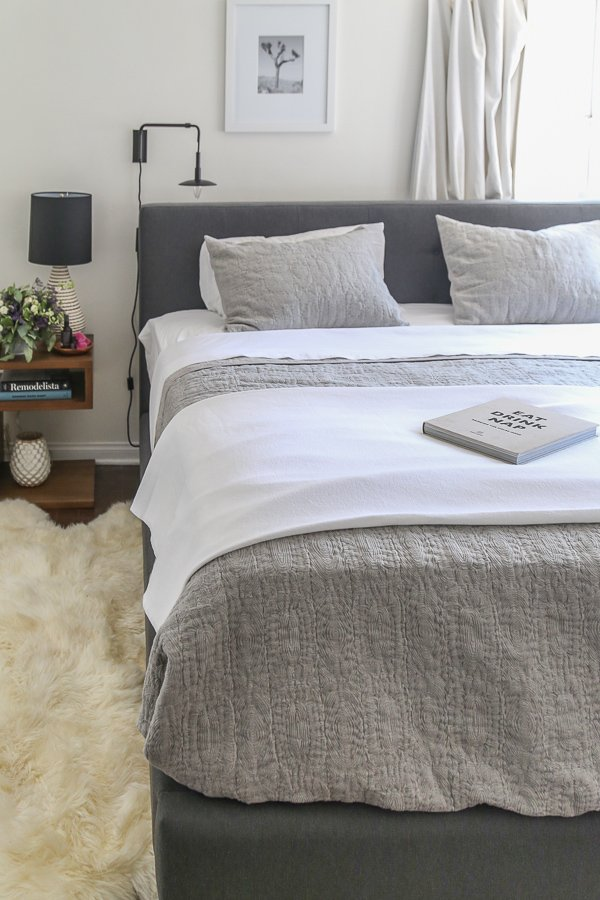 Bed in dark grey headboard with light grey bedding and shag rug