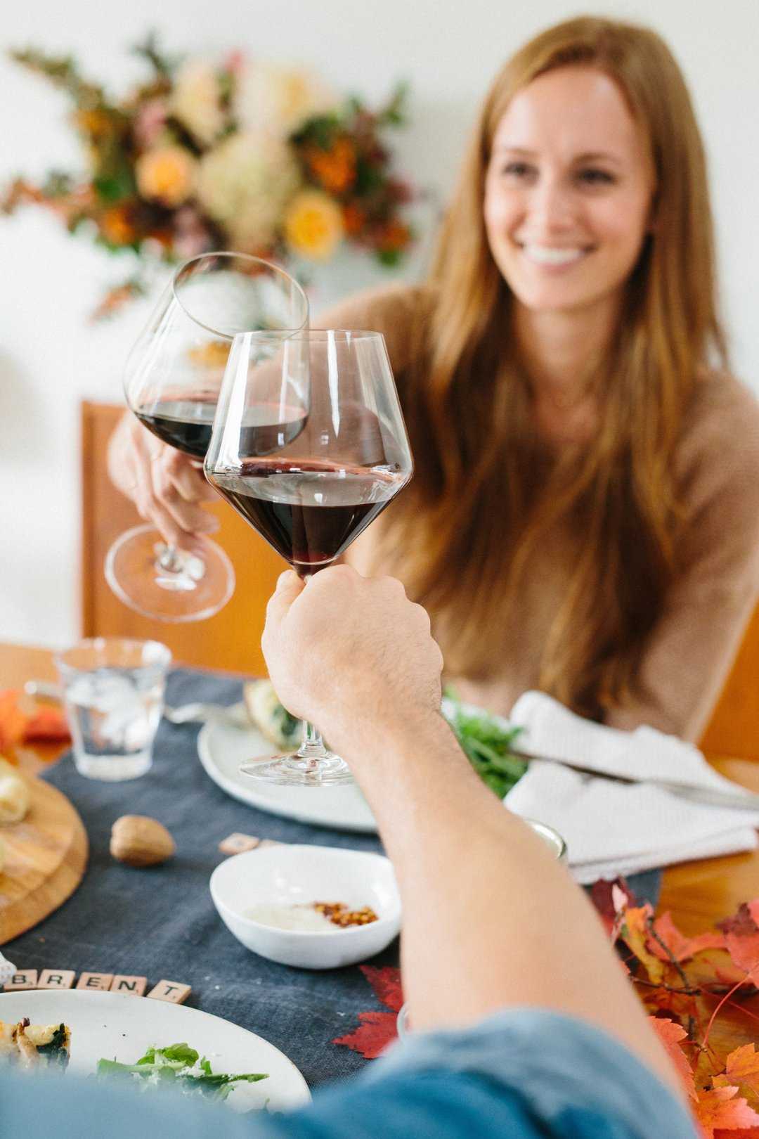 Couple clinking red wine glasses over dinner table