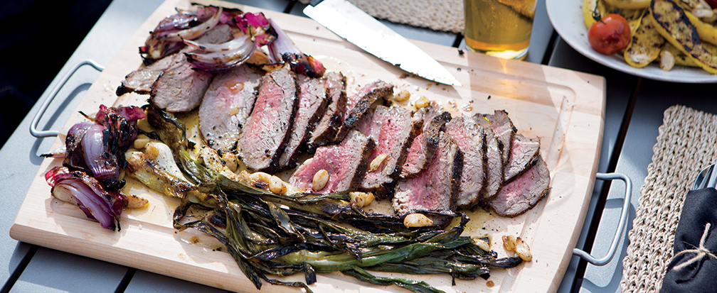 Grilled steak on a wood cutting board with charred onions, greens and nuts next to a beer glass