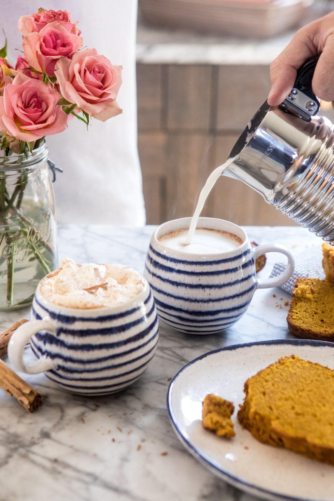 Pouring creamer into chai lattes in blue striped mugs with plate of sliced pumpkin bread on the right