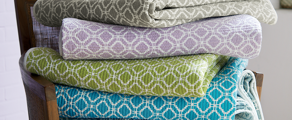 A stack of spare quilts in a variety of pastel colors on a chair