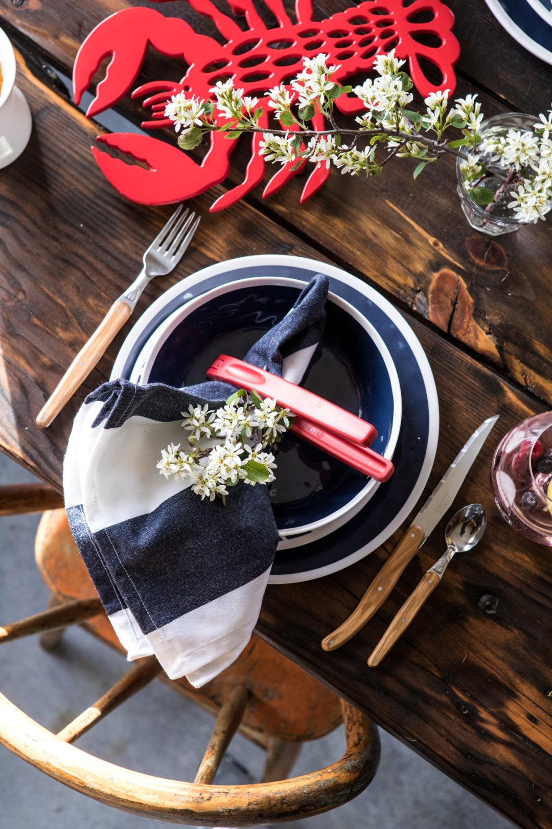 Dinner setting with blue plates, blue striped napkin, and red seafood cracker with white small flowers as center piece and red lobster trivet