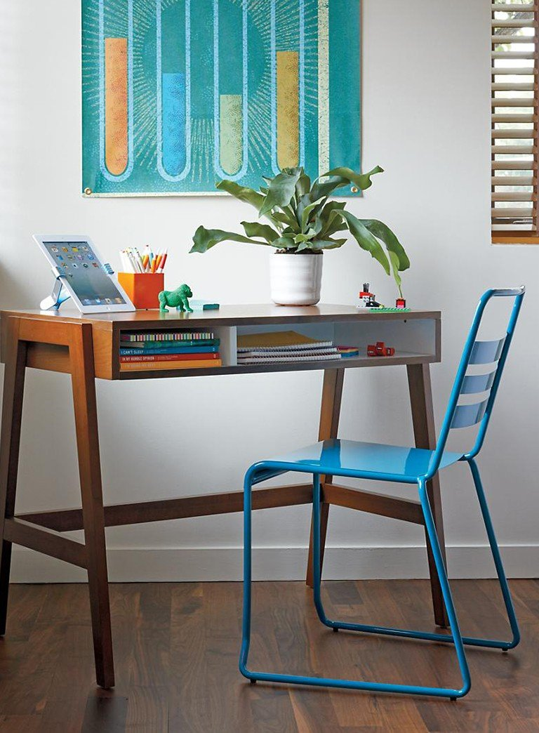 A modern kids desk is completed with a blue metal desk chair.