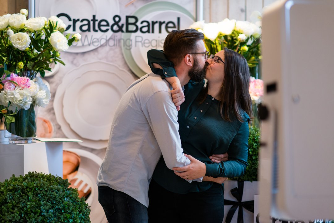 Couple kissing in front of Crate and Barrel gift registry sign