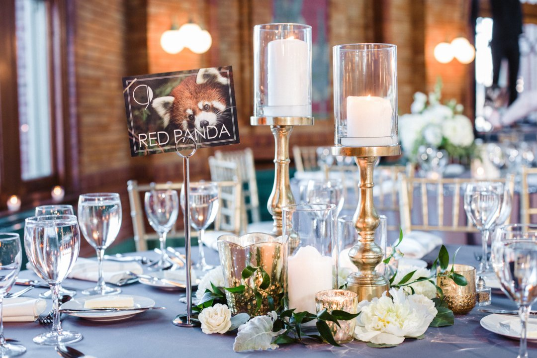Gold candles and clear wine glasses on wedding reception table